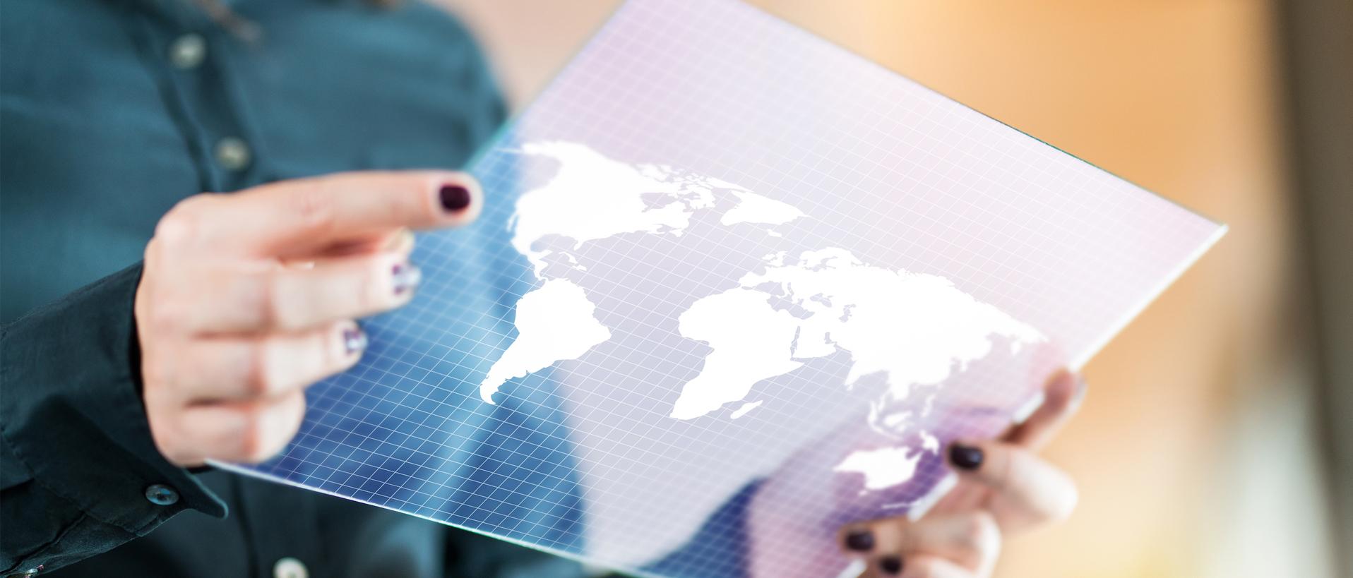 Eine Person hält eine auf Glas gedruckte Weltkarte