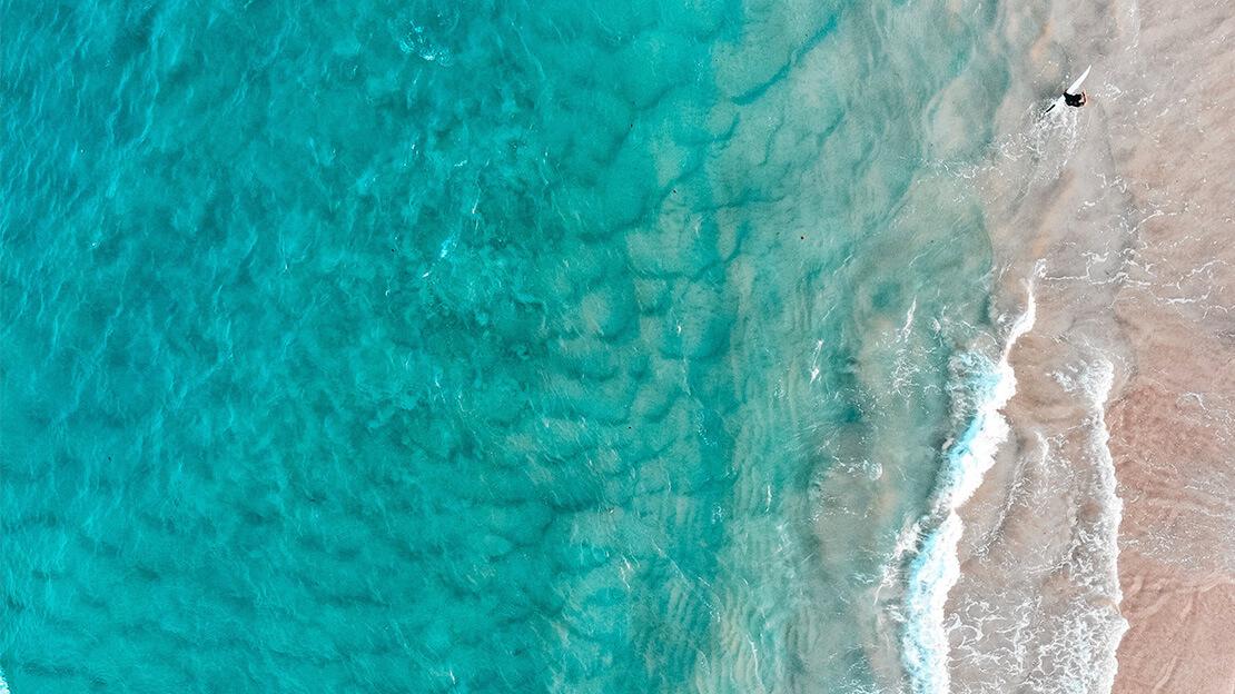 Strand und Meer aus der Vogelperspektive.