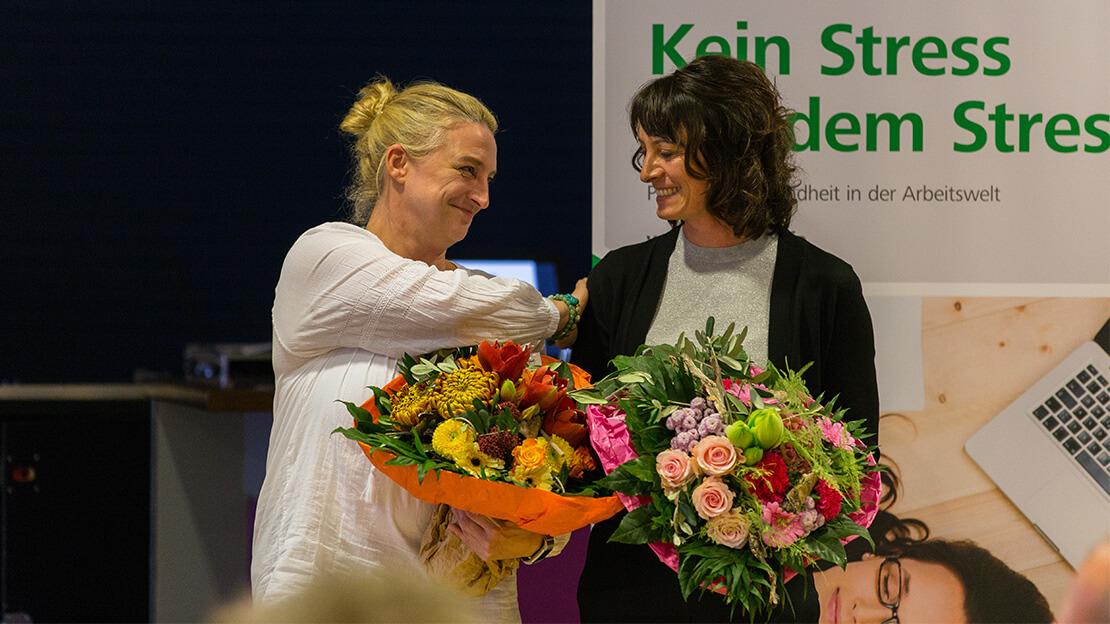 Zwei Frauen erhlaten einen Blumenstrauß