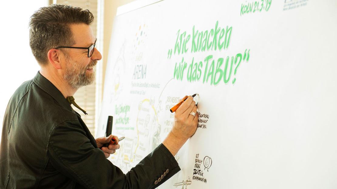 Ein Mann schreibt etwas an ein Whiteboard.