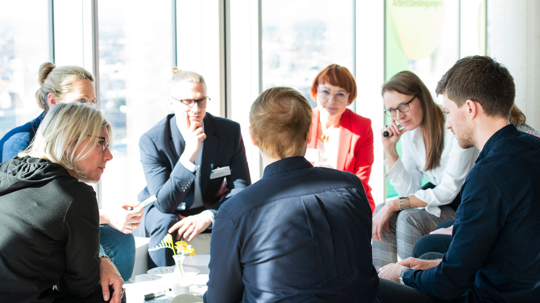 Männer und Frauen sitzen in einer Gesprächsrunde zusammen
