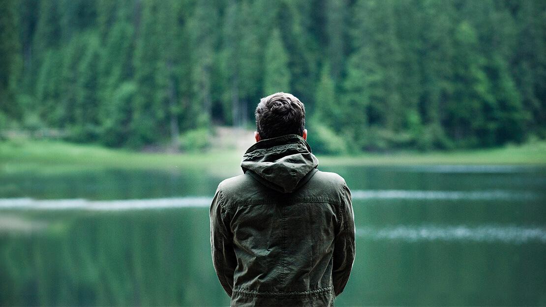 Ein Mann steht vor einem Waldsee