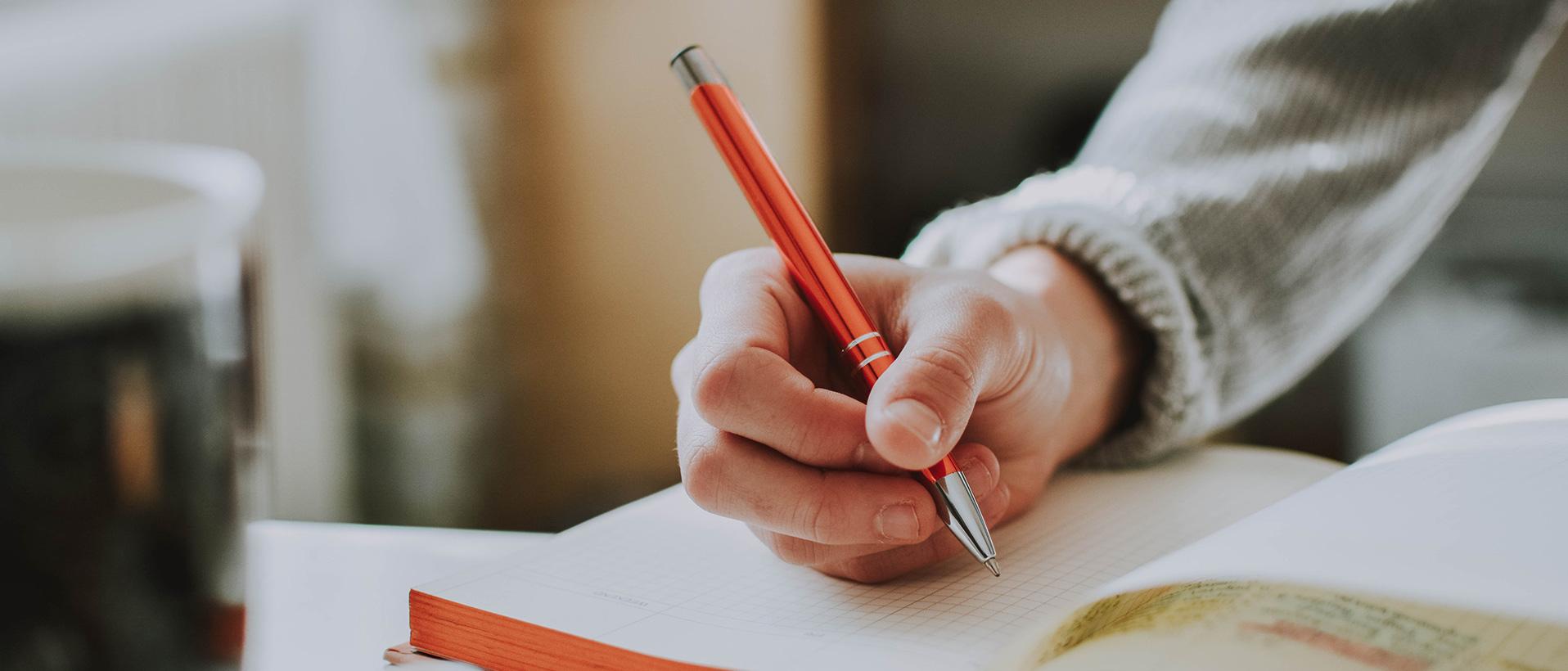 Hand die einen Stift hält und in ein Buch schreibt.
