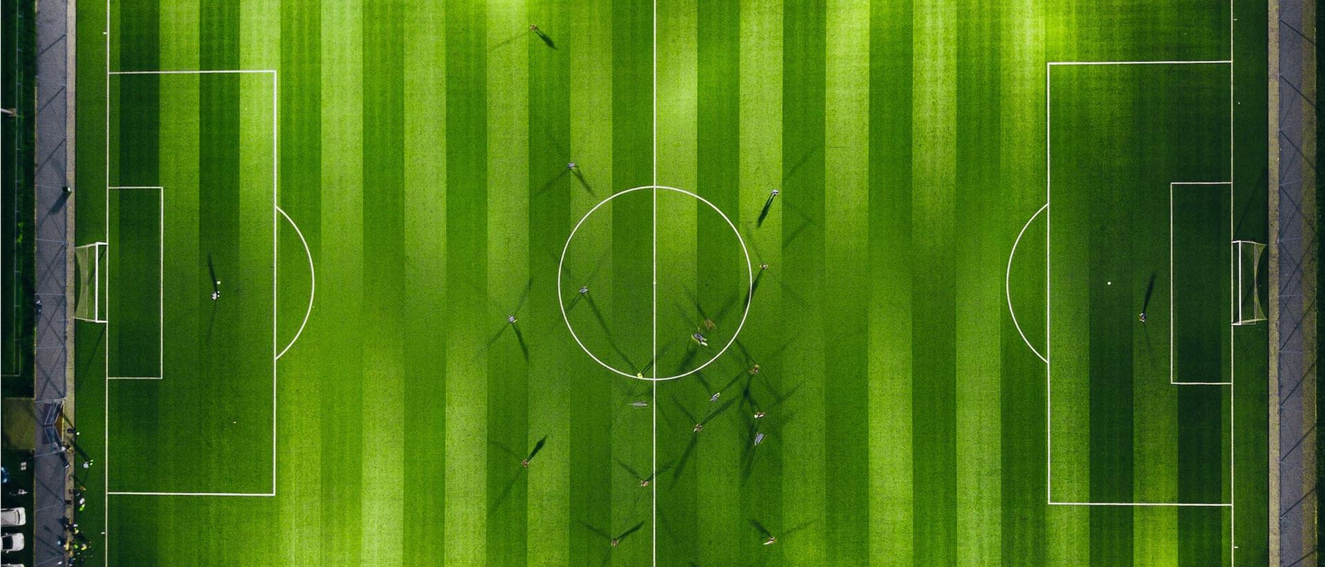 Fußballfeld von oben, auf dem sehr klein sie Spieler zu sehen sind