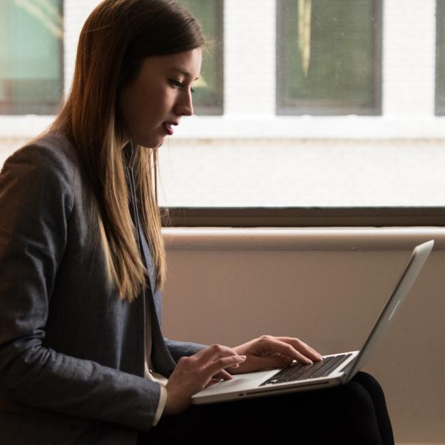 Eine junge Frau arbeitet an einem Laptop auf ihrem Schoß.
