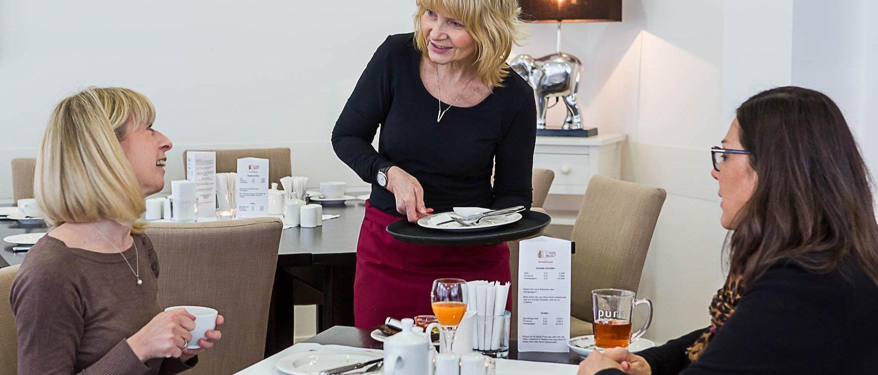Eine Kellnerin bedient in einem Café