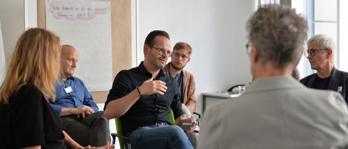 Männliche Person sitzt in erklärender Haltung in Mitten von Workshop-TeilnehmerInnen.