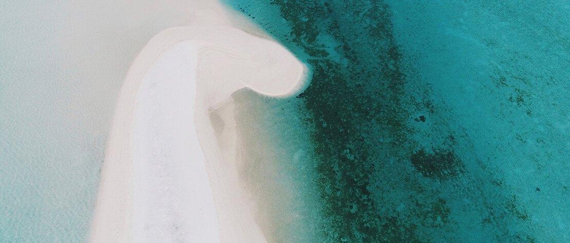 Luftaufnahme einer Landzunge im Meer.