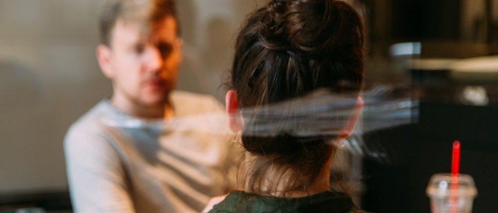 Der Blick durch die Scheibe zeigt eine Frau von hinten und einen Mann, die gerade ein intensives Gespräch führen.