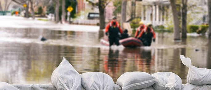 Eine überflutete Straße mit Sandsäcken im Vordergrund sowie Helfern mit Boot auf dem Wasser.