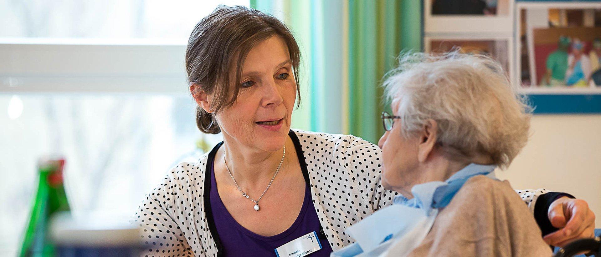 Eine Pflegerin mit einer betreuten Person beim Mittagessen