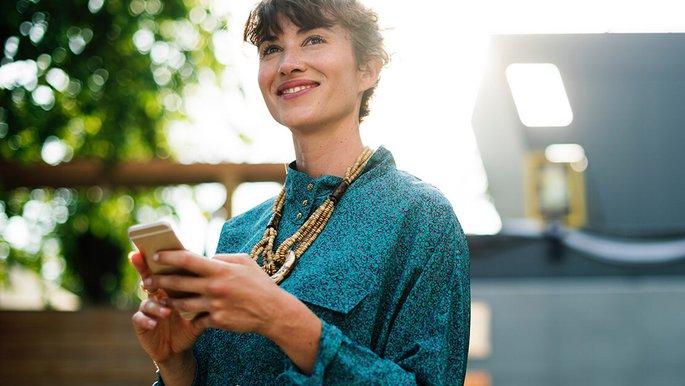 Eine Frau mit einem Smartphone in der Hand.