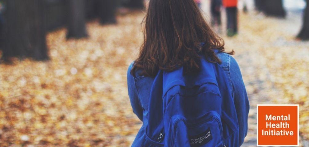 Ansicht eines jungen Mädchen von hinten mit blauem Rücksack, welches über einen laubbedeckten Weg geht.
