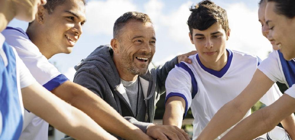 Trainer, Jungen und Mädchen eines Sportteams stehen im Kreis und legen Händer übereinander.