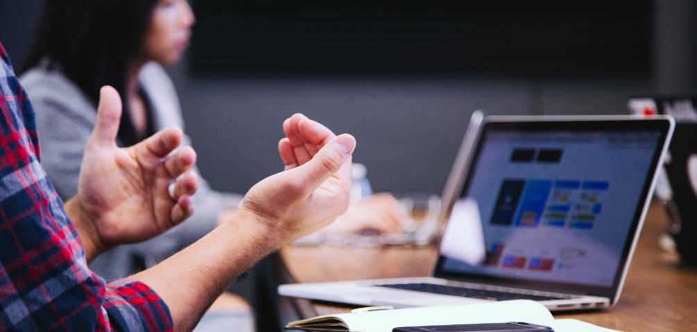 Eine Frau im Hintergrund sowie gestikulierende Hände im Vordergrund vor einem auf einem Tisch liegenden Laptop