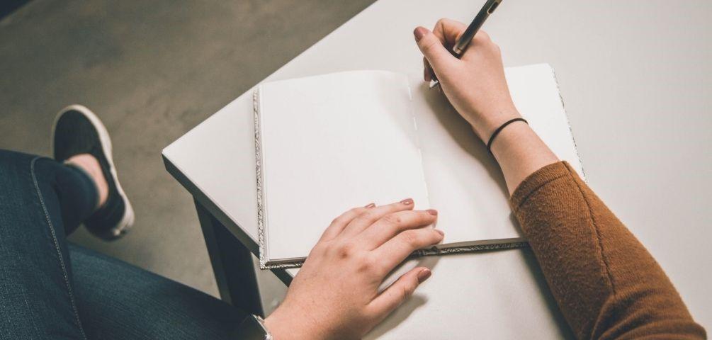 Frauenhände beginnen in ein Paperback zu schreiben