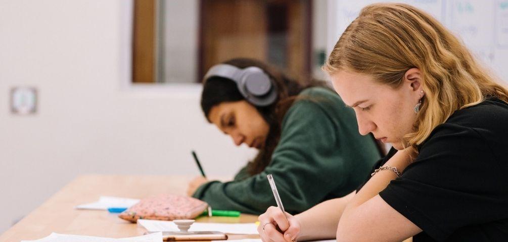 Zwei Berufsschüler im Klassenzimmer schreiben konzentriert etwas in Ihre Hefte