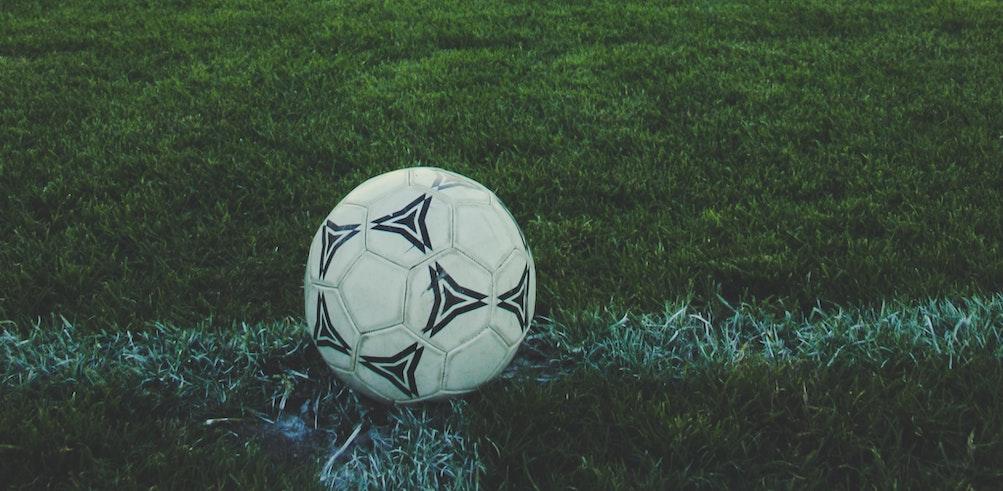 Fußball liegt auf einem Rasenfußballplatz, im Hintergrund steht ein Tor